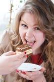 Buen tiempo y muchacha hermosa feliz que comen la torta Imagen de archivo libre de regalías