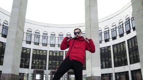 Buen tipo en rap rojos del equipo y de las gafas de sol del deporte al lado de columnas del granito almacen de metraje de vídeo