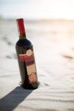 Buena botella de vino en la playa en el sol fotos de archivo