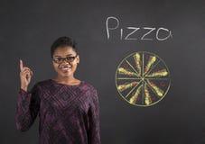 Buena idea de la mujer africana para la pizza en fondo de la pizarra Imagen de archivo