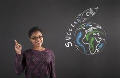 Buena idea de la mujer africana sobre éxito del mundo en fondo de la pizarra imagen de archivo