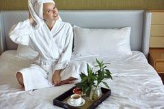 Buena mañana del desayuno Muchacha feliz con la albornoz que lleva y la toalla del estilo del desayuno de la mujer casera de la r imagen de archivo