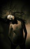 Buena muchacha con el pelo que fluye en un fondo gris. Fotos de archivo libres de regalías