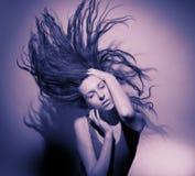 Buena muchacha con el pelo que fluye en un fondo gris. Imagenes de archivo