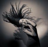 Buena muchacha con el pelo que fluye en un fondo gris. Foto de archivo
