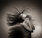Buena muchacha con el pelo que fluye en un fondo gris. Fotos de archivo