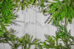 Buenas fiestas, decoración de la Navidad, tablero y ramas de árboles Foto de archivo libre de regalías