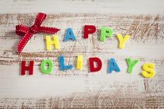 Buenas fiestas giftcard hecho por las letras multicoloras en el fondo de madera Imagenes de archivo