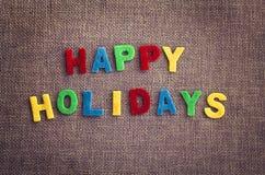 Buenas fiestas giftcard hecho por las letras multicoloras en la materia textil del lino del contraste Imagenes de archivo
