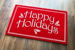 Buenas fiestas recepción Mat On Wood Floor Background del rojo de la Navidad imagenes de archivo