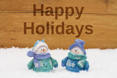 Buenas fiestas saludando, muñecos de nieve en nieve con vagos de madera resistidos Fotos de archivo