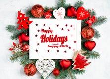 Buenas fiestas y texto feliz 2019 con el photoframe de la Navidad rodeado por las ramas de un ?rbol del A?o Nuevo, decoraciones r foto de archivo libre de regalías
