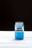 Buenas karmas - una inscripción en la etiqueta de un tarro de cristal con un líquido del color azul en un fondo blanco y negro Imagen de archivo