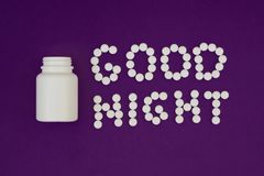 Buenas noches de la inscripci?n hechas de las p?ldoras blancas Botella de p?ldora en el fondo violeta Concepto del insomnio imagenes de archivo