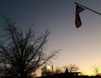 Buenas noches - puesta del sol de la pequeña ciudad con las siluetas del árbol y dos banderas americanas fotografía de archivo