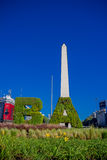 BUENOS AIRES, ARGENTINA - MAY 02, 2016: the initials of the name of the city made of plants in front of the obelisk. Iconic building in the city builded in Royalty Free Stock Photography