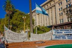 BUENOS AIRES, ARGENTINE - 2 MAI 2016 : le drapeau de l'Argentine a entouré par des bannières de protestation réclamant les Maloui Image stock