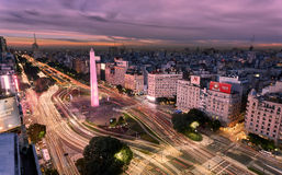 Buenos Aires in motion. Traffic making its way through the Avenida 9 de Julio, the widest avenue in the world. Curved lighttrails around the Obelisco, the symbol royalty free stock photos