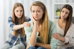 Buenos amigos que animan al adolescente preocupante Foto de archivo libre de regalías