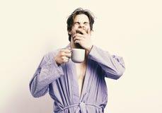 Buenos días El deportista con la cara soñolienta se coloca en albornoz con la taza imágenes de archivo libres de regalías
