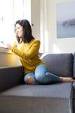 ¡Buenos días! ¿Quiera pasar cerca? Mujer que se relaja en el sofá y que hace una llamada de teléfono Imagen de archivo