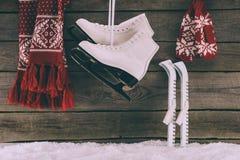 Bufanda con los guantes y los patines blancos que cuelgan en la pared de madera imagen de archivo libre de regalías
