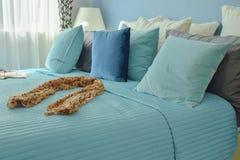 Bufanda en cama en lecho azul del esquema de color Imagenes de archivo