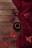 Bufanda hecha punto del color de Borgoña con hojas de otoño y una taza de Fotos de archivo