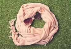 Bufanda y gafas de sol en colores pastel veraniegas en hierba Foto de archivo libre de regalías