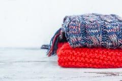 Bufandas calientes de los colores brillantes que mienten en pila en la tabla de madera Imágenes de archivo libres de regalías
