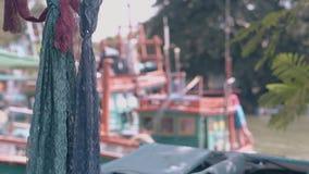 Bufandas de encaje y bahía borrosa del océano con los barcos amarrados el día metrajes