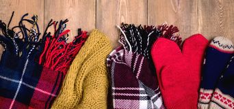 Bufandas hechas punto calientes y manoplas del fondo acogedor del invierno en fondo de madera con el espacio para la opinión supe Foto de archivo