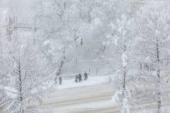 Bufera di neve nella città La gente sta stando ad una fermata dell'autobus in una bufera di neve Immagini Stock