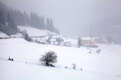 Bufera di neve sopra le montagne ed il villaggio nell'inverno, alpi, Swit del alpin Immagine Stock Libera da Diritti