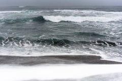 Bufera di neve su una spiaggia dell'oceano Pacifico con la sabbia nera Immagini Stock