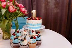 Bufet z r??norodno?? wy?mienicie cukierkami, karmowi pomys?y, ?wi?towanie najpierw tort urodzinowy Wyśmienicie słodki bufet z zdjęcie royalty free