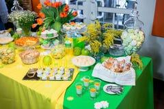 Bufet z zieleni tablecloth z przekąskami, deserami i bukietem tulipany, fotografia royalty free
