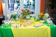 Bufet z zieleni tablecloth z przekąskami, deserami i bukietem tulipany, zdjęcia stock