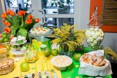Bufet z zieleni tablecloth z przekąskami, deserami i bukietem tulipany, obrazy royalty free
