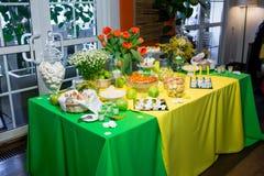 Bufet z zieleni tablecloth z przekąskami, deserami i bukietem tulipany, obrazy stock