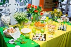 Bufet z zieleni tablecloth z przekąskami, deserami i bukietem tulipany, zdjęcia royalty free