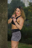 Buff Beauty Touches Up Makeup During Outdoors Photo Session  Royalty Free Stock Photo