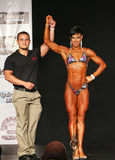 Buff Middle-Aged Figure Champion. Shapely Sandra Oquendo strikes a winning pose as she raises her arm in victor after competing in the Figure competition at the stock photos