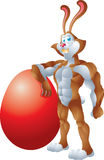 Buff rabbit leaning on giant egg Stock Photos