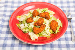 Buffalo Chicken Nuggets on Caesar Salad Stock Photo