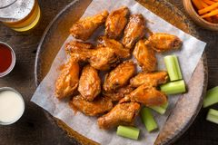 Buffalo Chicken Wings. Delicious spicy buffalo chicken wings with beer, celery, carrot sticks and dipping sauces royalty free stock images