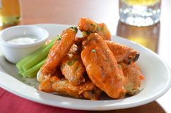 Buffalo Chicken Wings with Out of Focus Beers Royalty Free Stock Photo