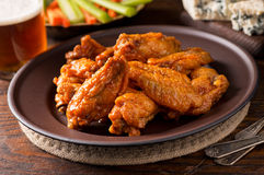 Buffalo Chicken Wings. A plate of delicious buffalo style chicken wings with hot sauce, blue cheese, celery sticks, carrot sticks, and beer Stock Photos