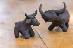 buffalo clay sculpture on wooden background stock images