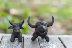 Buffalo clay sculpture on wooden floor stock photos